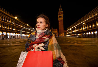 Modern woman in winter coat with standing on Piazza San Marco