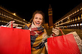 Excited woman in winter coat showing shopping bags in Venice