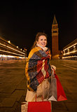 Woman with shopping bags on Piazza San Marco in evening, Venice