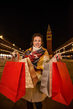 Happy woman in winter coat showing shopping bags while in Venice