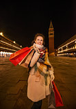 Playful woman holding shopping bags on Piazza San Marco, Venice