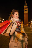 Happy woman with shopping bags looking on something. Venice