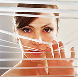 woman observes through blinds