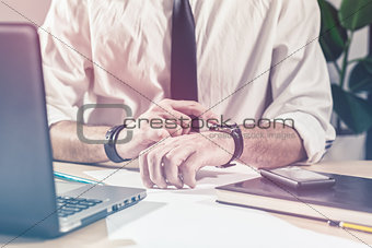 Businessman checking time on watch at office desk