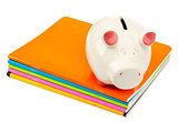 Piggy bank on pile of copybooks