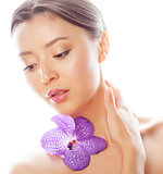 young pretty asian woman with flower orchid close up isolated spa