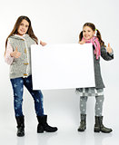 cheerful girls holding blank board