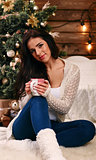 Young beautiful woman with sitting home  with cup of hot coffee wearing knitted warm sweater. Christmas tree with decorations and lights in the room, snowy winter outside