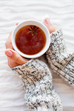 Women holds a cup of hot tea with anise star. Cozy morning at ho
