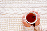 Women holds a cup of hot tea with anise star. Beautiful fabric b
