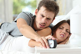 Angry couple turning off the alarm clock