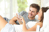 Couple sharing a smart phone on the bed
