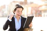 Euphoric successful executive watching a tablet