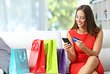 Fashion girl shopping online with bags beside