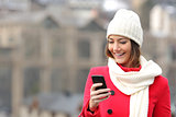 Girl texting in a mobile phone in winter