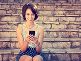 Smiling Hipster Girl Texting with Her Mobile Phone