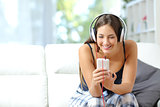 Girl listening music from smartphone at home