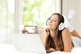 Girl listening music with headphones and laptop