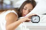 Wake up of an asleep girl stopping alarm clock