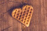 Heart shaped homemade waffle on wooden desk