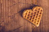 Heart shaped homemade waffle on wooden desk