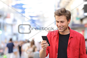 Man in red texting on a mobile phone