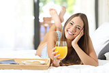 Happy girl having breakfast with orange juice