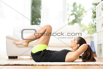 Fitness girl doing crunches at home