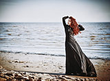 Beautiful sad goth girl standing on sea beach