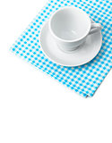 White porcelain mug with saucer tableware on cellular napkin