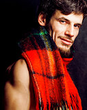 portrait of handsome man warmed up in scarf, smiling closeup dark background