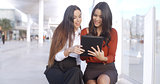 Two women discussing information on a tablet