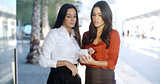 Two pretty stylish women reading an sms