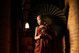 Buddhist novice walking with umbrella