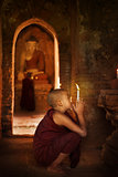 Buddhist novices praying in monastery