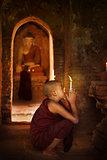Buddhist novices praying in monastery