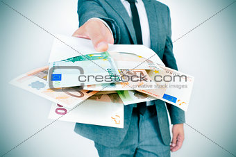man giving an envelope full of euro bills
