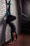 Attractive woman do handstands in the gym
