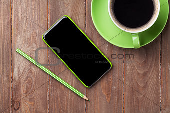 Office wooden desk with smartphone and coffee
