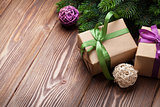 Christmas gift boxes and fir tree on table