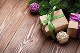 Christmas gift boxes and fir tree on table
