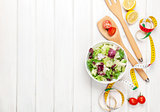 Fresh healthy salad, utensils and tape measure over white wooden