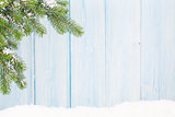 Christmas fir tree in snow in front of wooden wall