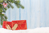 Christmas gift boxes and fir tree branch in snow
