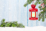 Christmas candle lantern on fir tree branch in snow