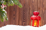 Christmas candle lantern and fir tree branch in snow