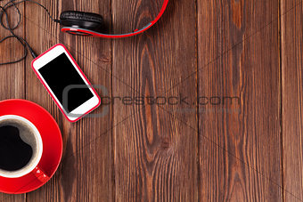 Smartphone, headphones and coffee cup