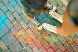 Close-up of feet on the ground surrounded by paints