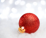 Christmas Decoration with Red Ball in the Snow on the Blurred Background with Holiday Lights. Greeting Card