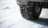 Close-up Image of Winter Car Tire on Snowy Road. Drive Safe Concept